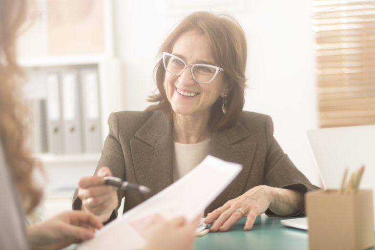Smiling personal health coach sitting in an office and talking to a woman